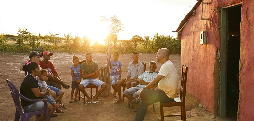 dez pessoas sentados em meia lua conversando sobre o projeto escolas do sertão ao pôr do sol