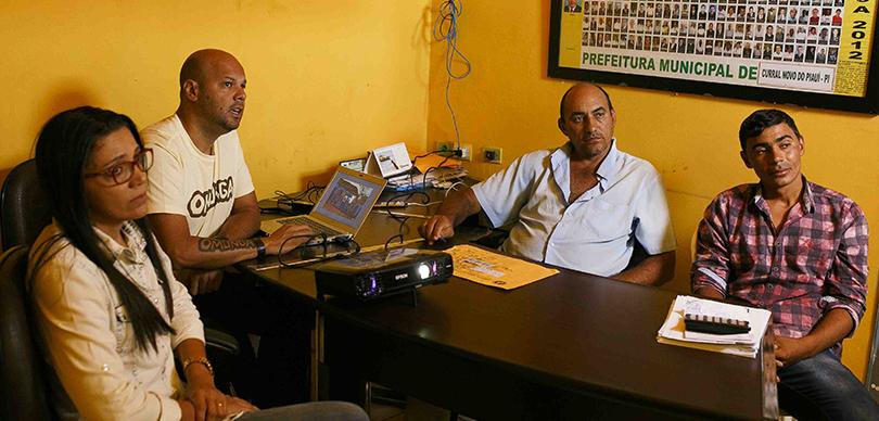 quatro pessoas ao redor da mesa falando sobre o projeto escolas no sertão
