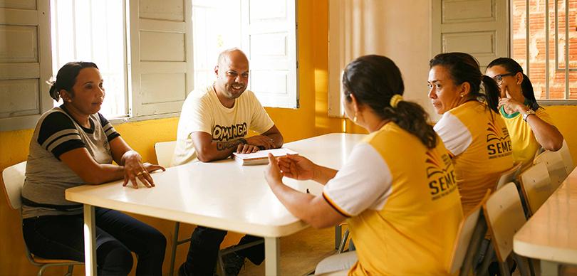 5 pessoas sorrindo sentadas ao redor de uma mesa conversando sobre o projeto escolas do sertão