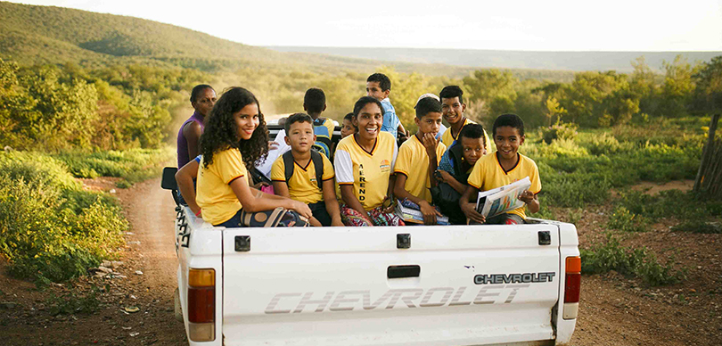 dez crianças com camisas amarelas encima da traseira de uma caminhonete em movimento