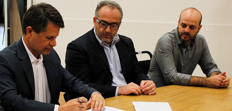 dois homens observando um terceiro escrevendo em um papel