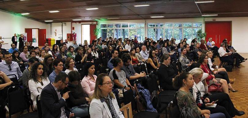 espectadores ouvindo e participando do evento sobre impacto social