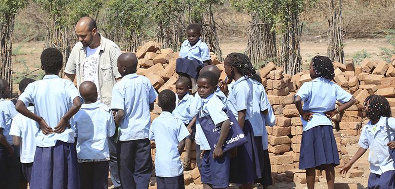 homem que é empreendedor social da omunga tento contato com crianças africanas com uniforme escolar azul