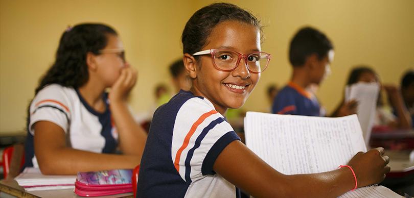 várias crianças concentradas enquanto uma menina sorri virando uma folha de caderno e olhando para a câmera dentro de uma escola no sertão do piauí