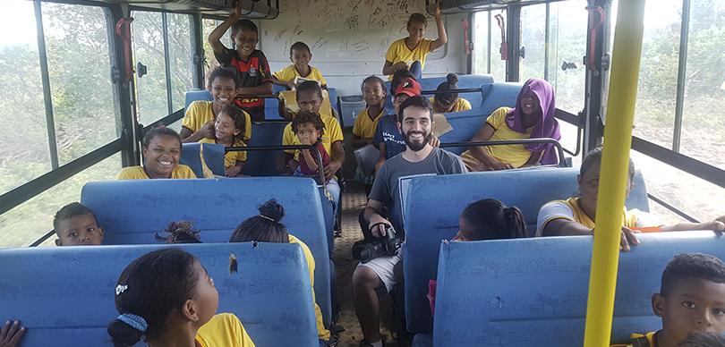 várias crianças dentro de um ônibus junto do fotógrafo voluntário do instituto omunga, todos sorrindo para a foto