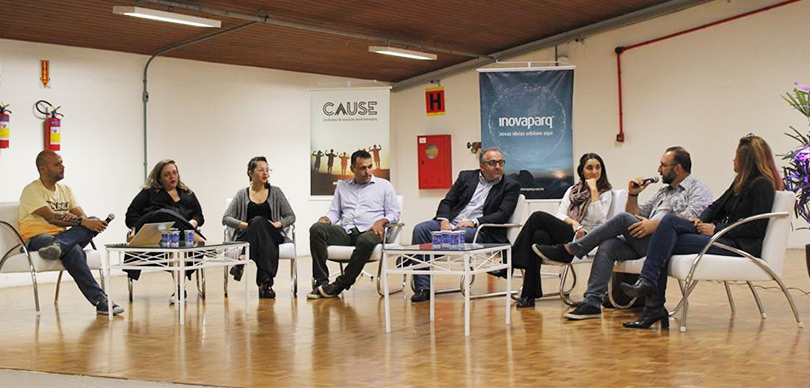 mesa redonda com algumas pessoas sentadas prestando atenção na fala de um dos participantes
