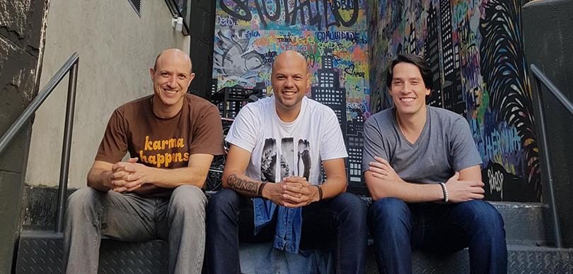 Três homens sentados em uma escadaria com o fundo grafitado posando para foto com as mãos junta em frente do corpo