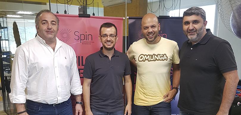 quatro homens sorrindo posando para foto, sendo que uma deles veste uma camisa da omunga