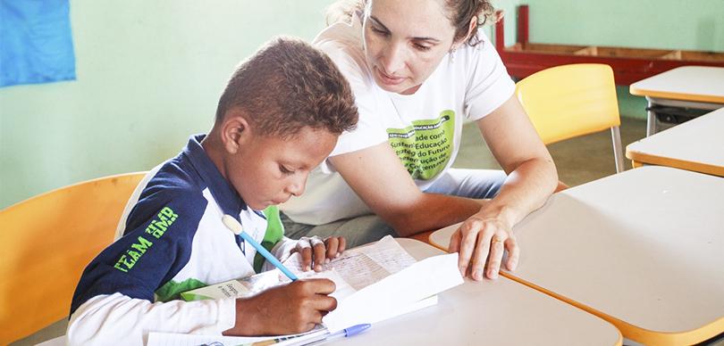 professora e aluno sentados enquanto a mulher auxilia o garoto em uma lição em uma escola do projeto Escolas do Sertão