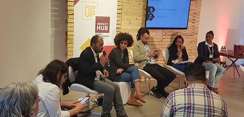 grupo de pessoas sentadas em cadeiras enquanto prestam atenção em um homem falando no microfone em fórum de empreendedorismo social