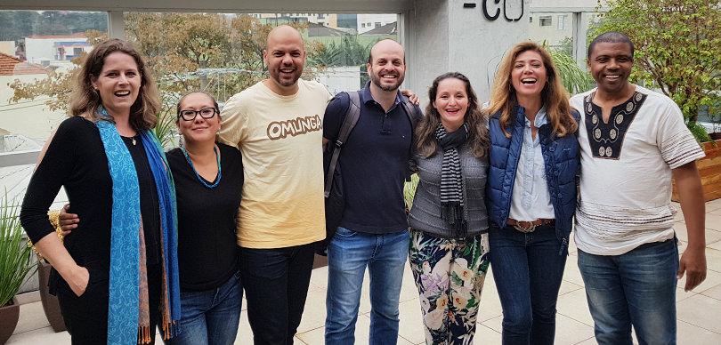 grupo de pessoas abraçadas posando para foto em encontro sobre empreendedorismo social
