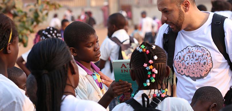 roberto pascoal, empreendedor social e mentor da omunga mostrando livros à crianças negras em situação de vulnerabilidade social
