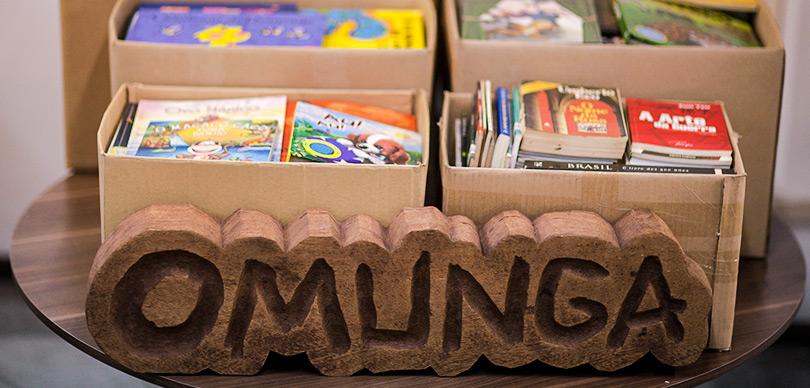 vários livros em caixas abertas com um pedaço médio de madeira com a logo da omunga que busca ter projetos incentivados pela lei rouanet