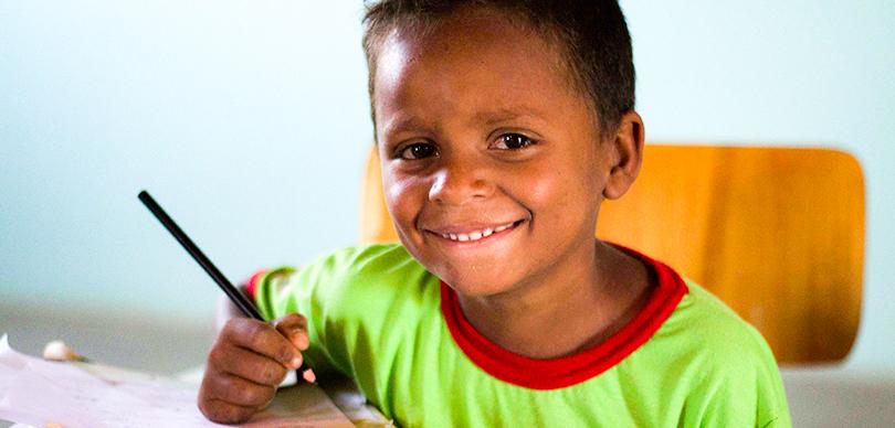 garoto beneficiado pelo projeto omunga olha para a câmera com lágrimas nos olhos