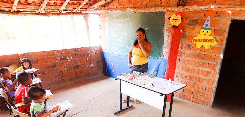 professora a frente da sala de aula ensina alunos em escola precária do sertão