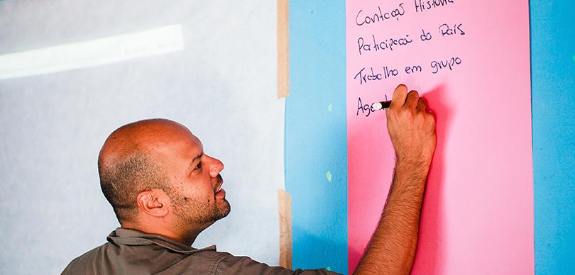 roberto pascoal, empreendedor social da omunga, escreve em cartolina rosa e leva transformação social por meio da educação