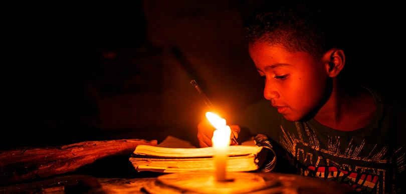 Criança estudando à luz de vela | OMUNGA Clube