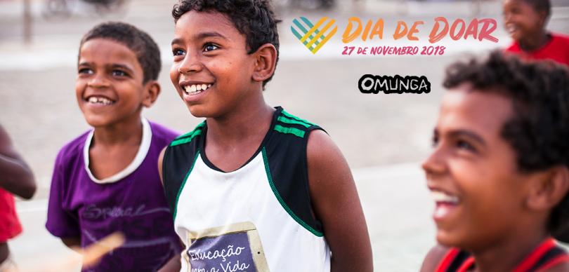 crianças sorriem olhando para frente, a logo do dia de doar e da omunga estão no canto superior direito