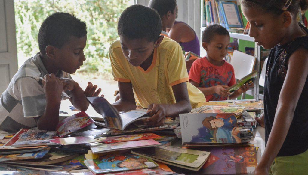 crianças na biblioteca com muitos livros
